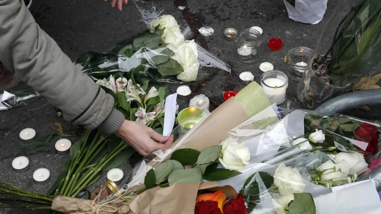A woman places a candle and reads a message outside the Bataclan concert hall, Saturday, Nov. 14, 2015 in Paris.