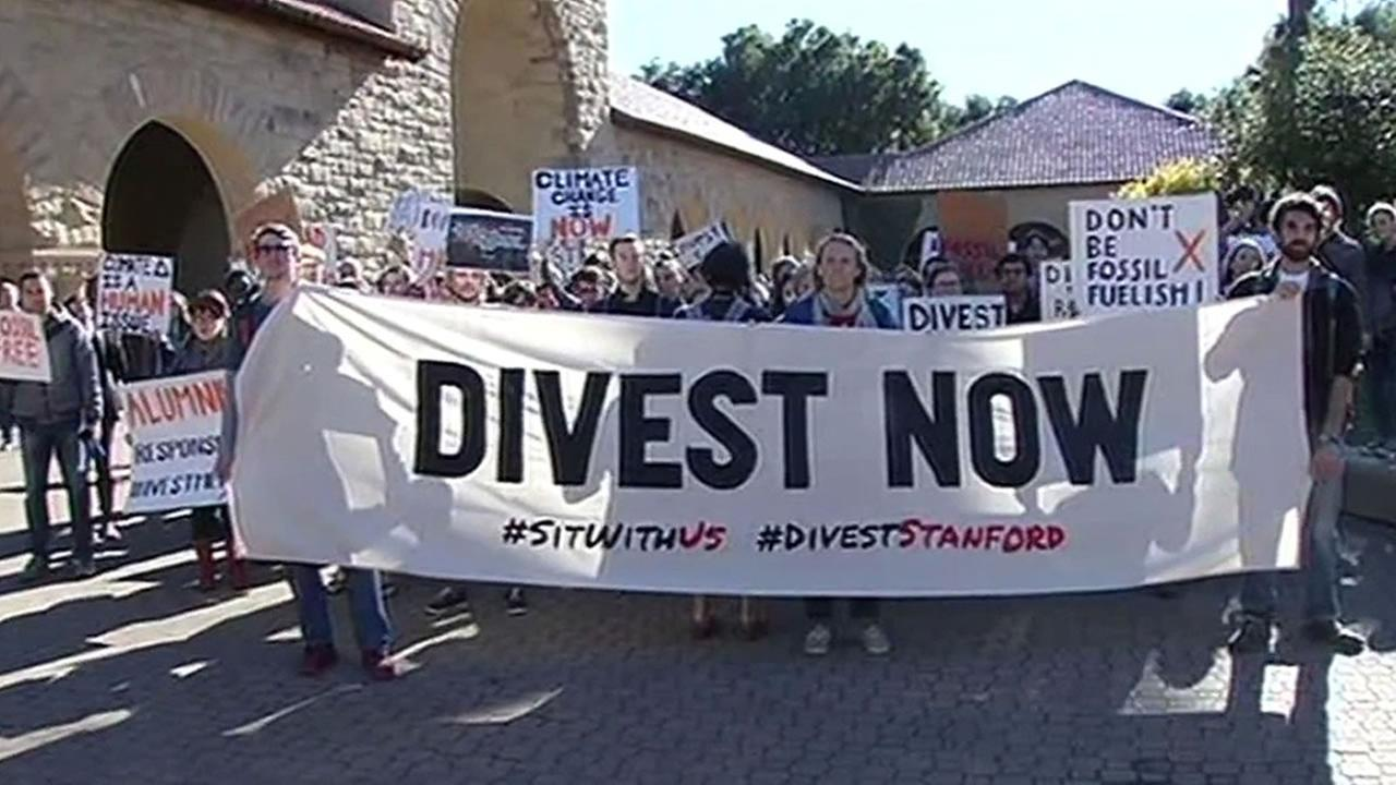 Protesters hold sign Divest Now