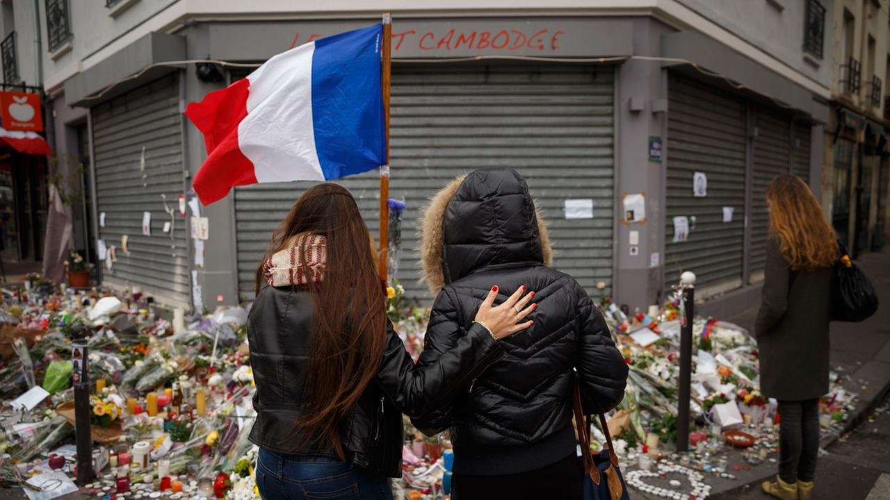 Two women stand outside the Petit Cambodge restaurant, a site of last Fridays attacks, in Paris, Tuesday, Nov. 17, 2015.