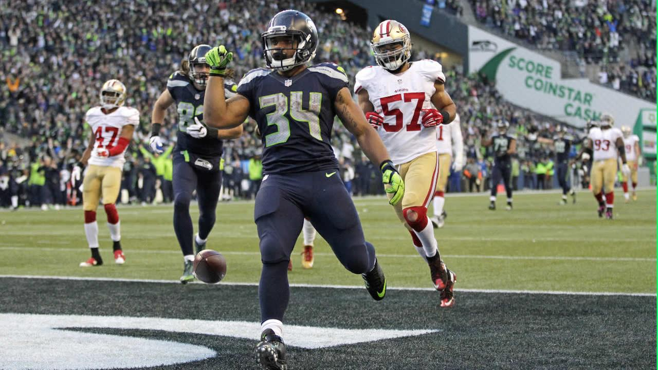 Thomas Rawls drops the ball after scoring a touchdown ahead of 49ers Michael Wilhoite during an NFL football game Sunday, Nov. 22, 2015, in Seattle. (AP Photo/John Froschauer)