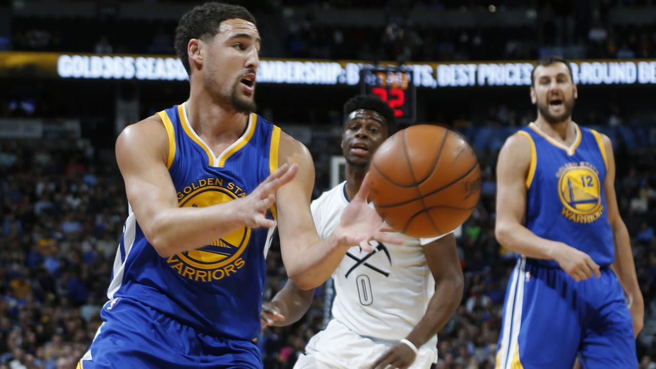 Warriors Klay Thompson fields pass as Nuggets Emmanuel Mudiay defends during the first half of an NBA basketball game Sunday, Nov. 22, 2015, in Denver. (AP Photo/David Zalubow)