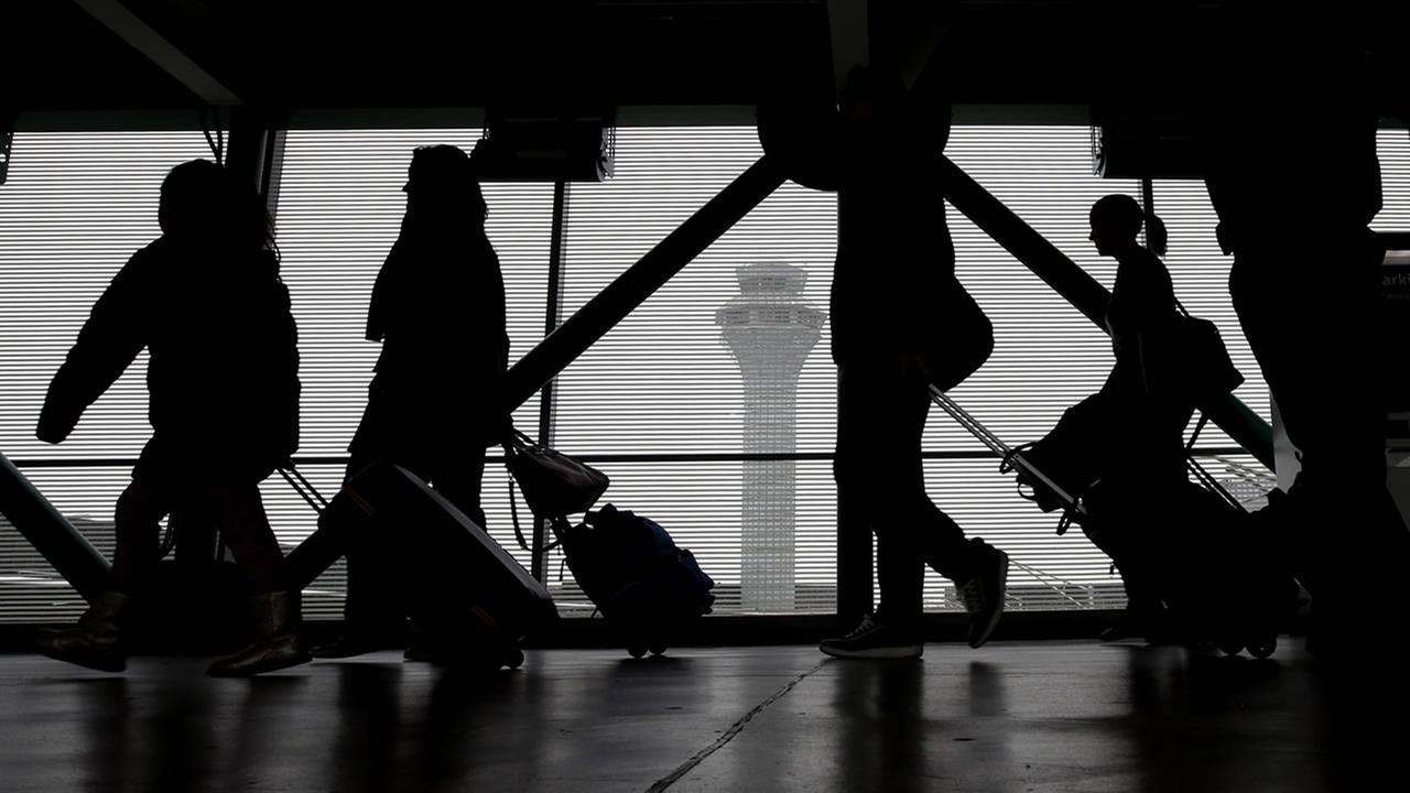 Passengers walk through Terminal 3 at OHare International Airport on Saturday, Nov. 21, 2015, in Chicago. (AP Photo/Nam Y. Huh)