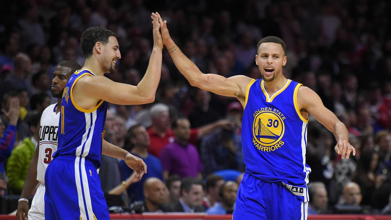 Warriors guard Stephen Curry high fives guard Klay Thompson during an NBA basketball game, Thursday, Nov. 19, 2015 in Los Angeles.