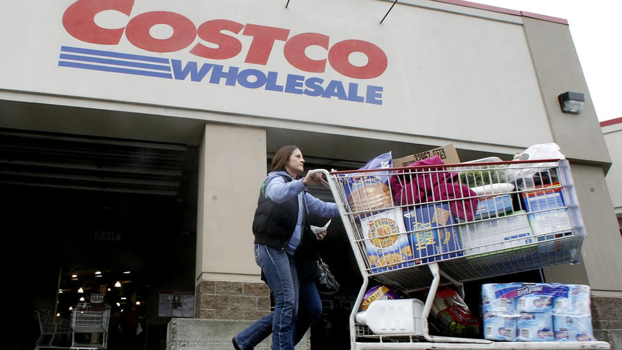 FILE - In this Dec. 7, 2011 file photo, a shopper leaves a Costco store in Portland, Ore. (AP Photo/Rick Bowmer, File)