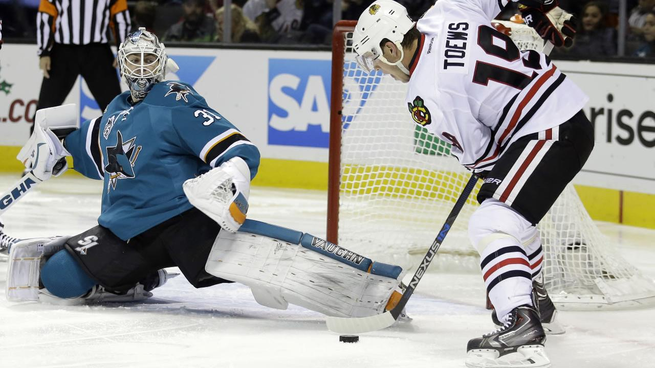San Jose Sharks goalie Martin Jones (31) stops a shot from Chicago Blackhawks Jonathan Toews (19) during the second period of an NHL hockey game, Wednesday, Nov. 25, 2015.