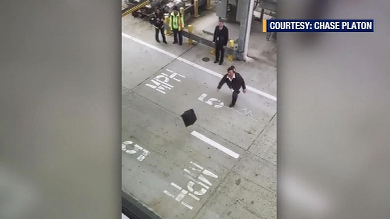 Alaska Airlines employees tossing a suitcase on a service road
