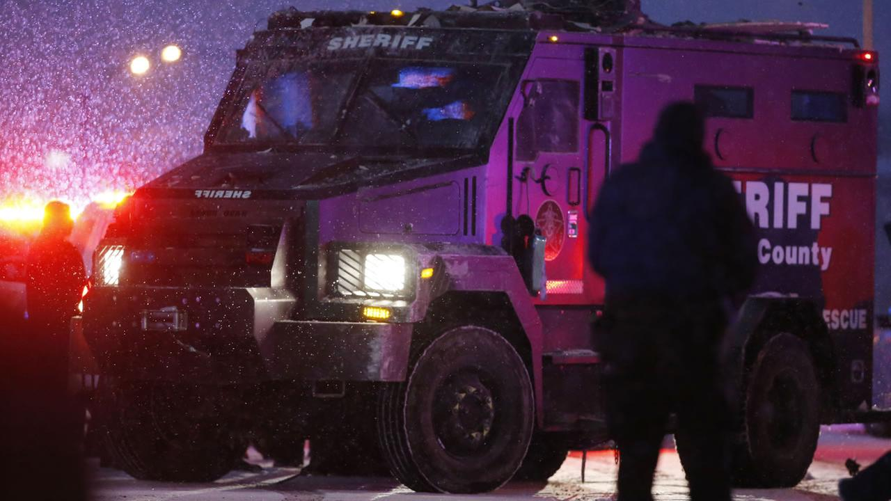 A police vehicle, carrying a suspect, is lead away after a shooting at a Planned Parenthood clinic Friday, Nov. 27, 2015, in Colorado Springs, Colo.