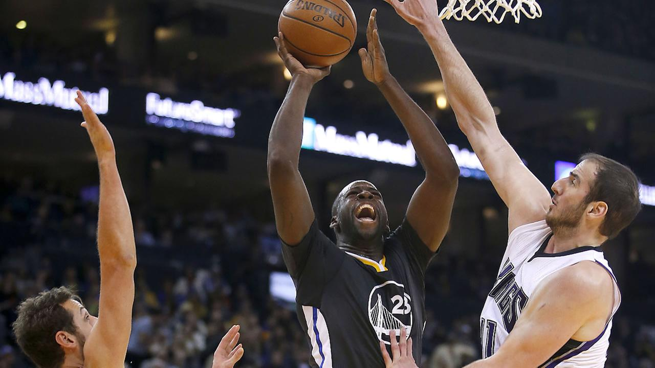 Golden State Warriors forward Draymond Green (23) shoots between Sacramento Kings Kosta Koufos, right, and Marco Belinelli (3) during the second half of an NBA basketball game Saturday, Nov. 28, 2015, in Oakland, Calif. The Warriors won 120-101.