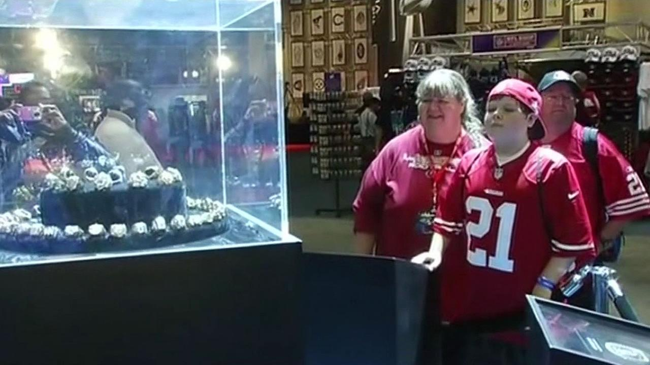 Family looks at Super Bowl rings in a glass case