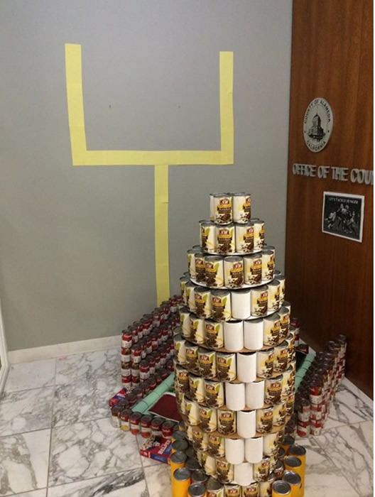 """<div class=""""meta image-caption""""><div class=""""origin-logo origin-image """"><span></span></div><span class=""""caption-text"""">OCC TACKLES HUNGER: Office of the County Counsel built the Coliseum and a giant football out of cans. This display was made from 806.25 pounds of food.</span></div>"""