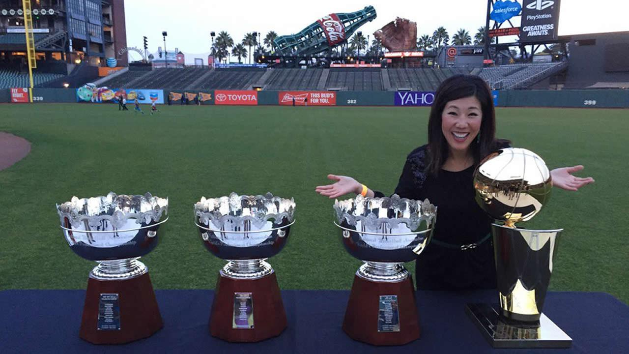 ABC7 Morning News Anchor Kristen Sze poses Golden State Warriors trophies during the Holiday Heroes event at AT&T Park in San Francisco on Monday, December 7, 2015.