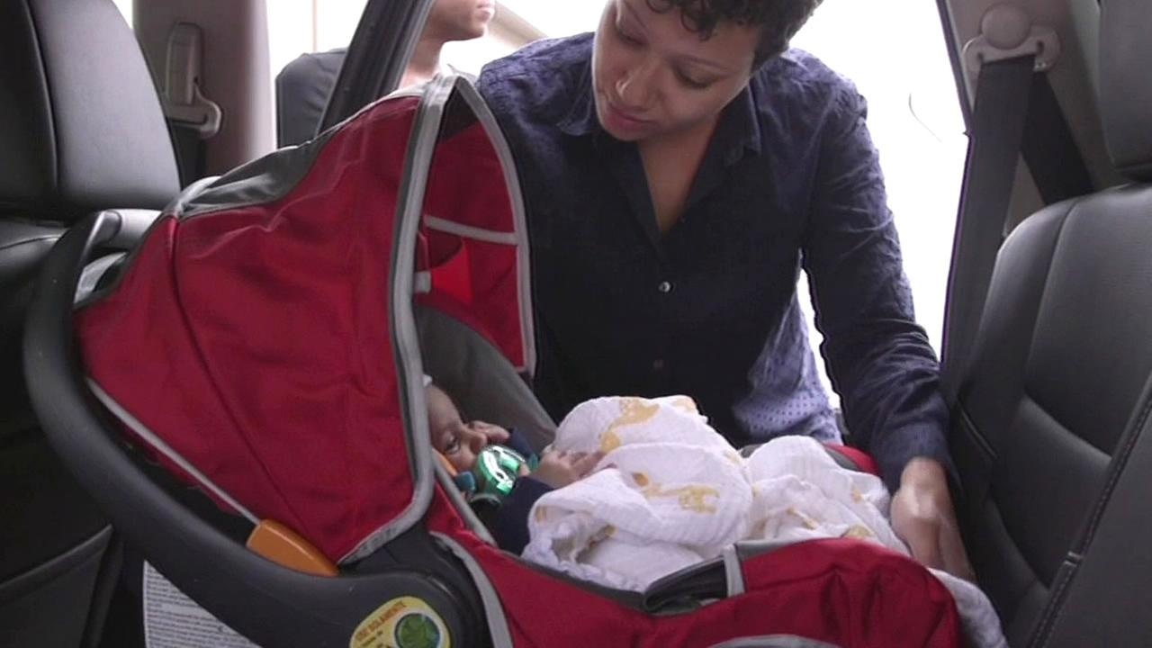 woman puts infant carrier in car
