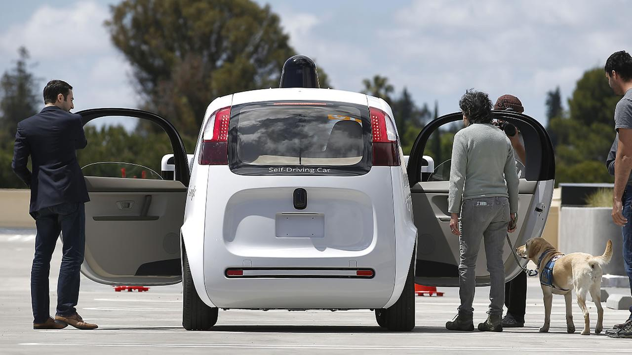 FILE - In a Wednesday, May 13, 2015 file photo, riders enter the Googles new self-driving prototype car for a ride during a demonstration at Google campus in Mountain View, Calif.