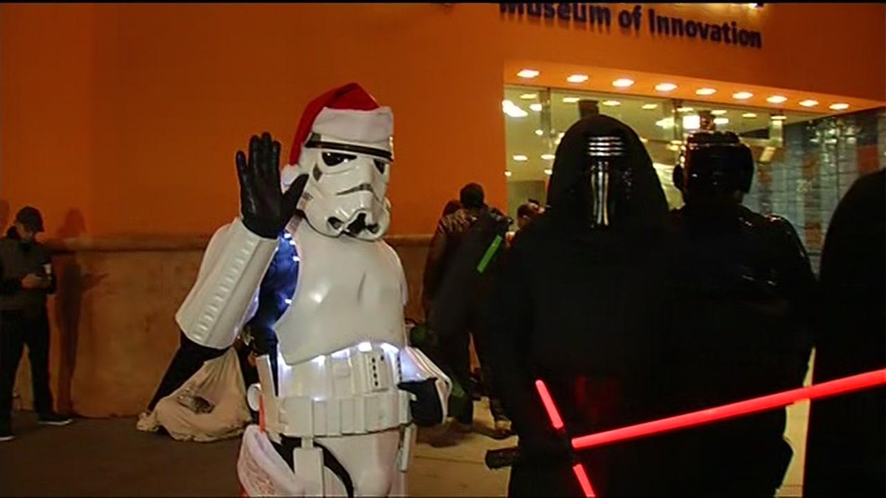 Star Wars fans in costume wave as they wait outside the Tech Museum in San Jose, Calif. on Thursday, December 17, 2015. KGO-TV/Jonathan Bloom