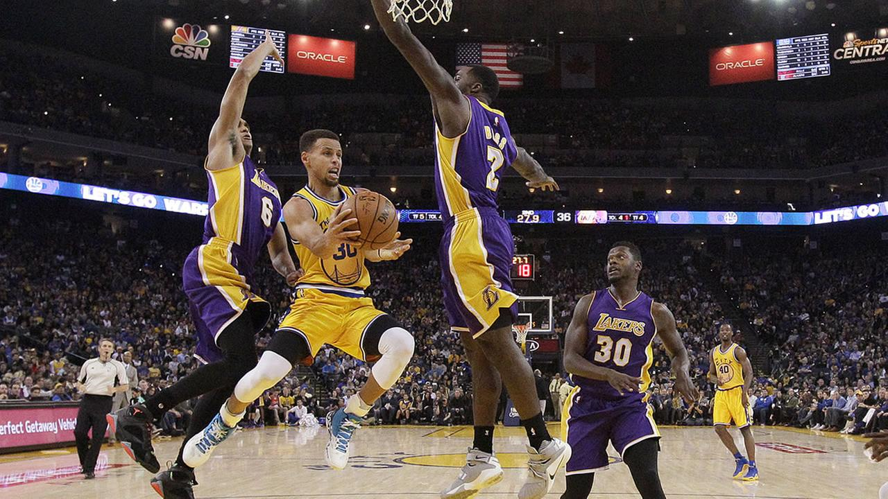 Warriors guard Stephen Curry looks to pass as Los Angeles Lakers players defend during an NBA game in Oakland, Calif., , Nov. 24, 2015. The Warriors won 111-77. (AP Photo/Jeff Chiu)