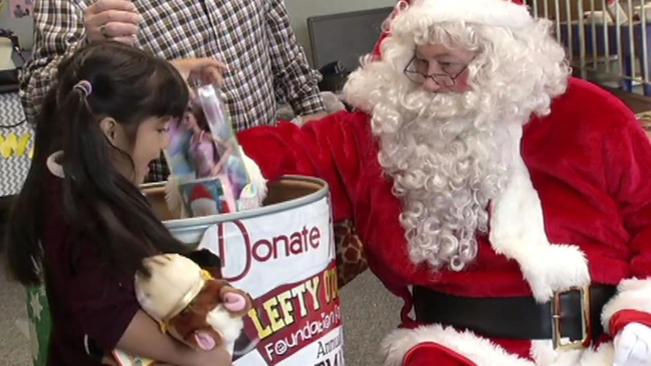 Santa handed out toys to children at San Francisco City Academy on Friday, December 18, 2015 that were donated by the owner of Lefty ODouls.