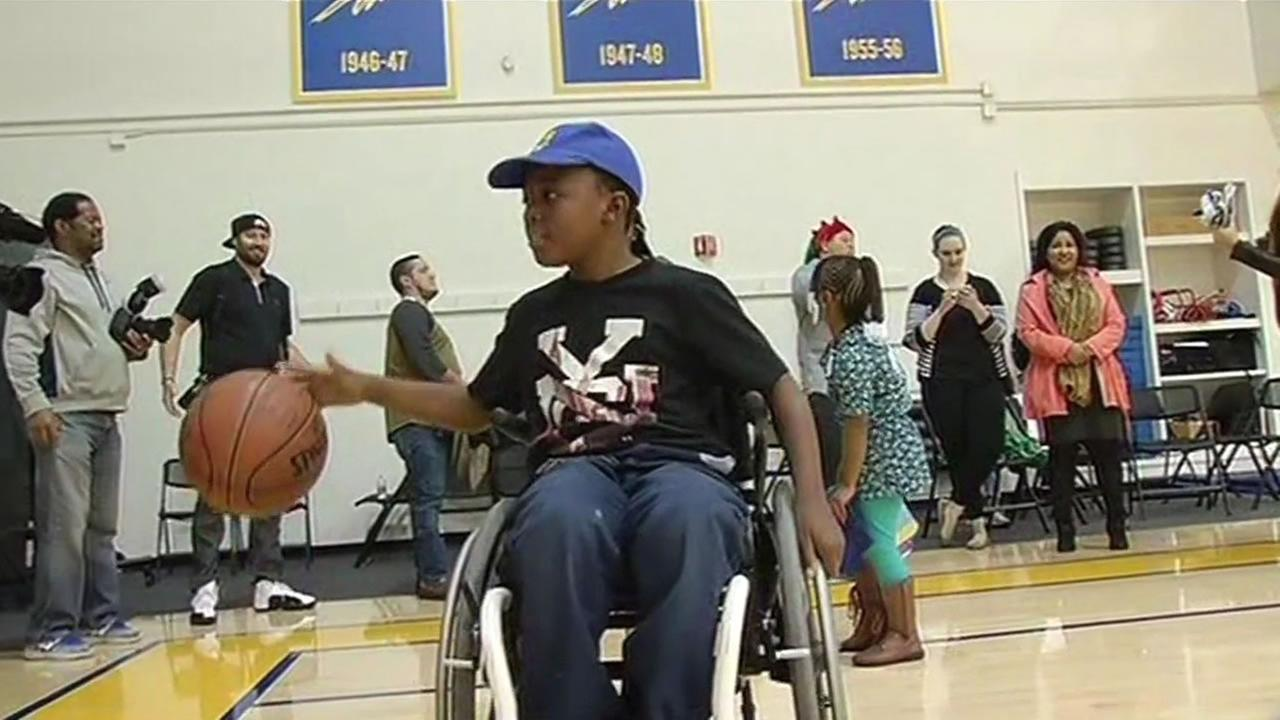 Kumar Polk, 8, shows off a basketball given to him by Golden State Warriors guard Steph Curry in Oakland, Calif. on Tuesday, December 22, 2015.