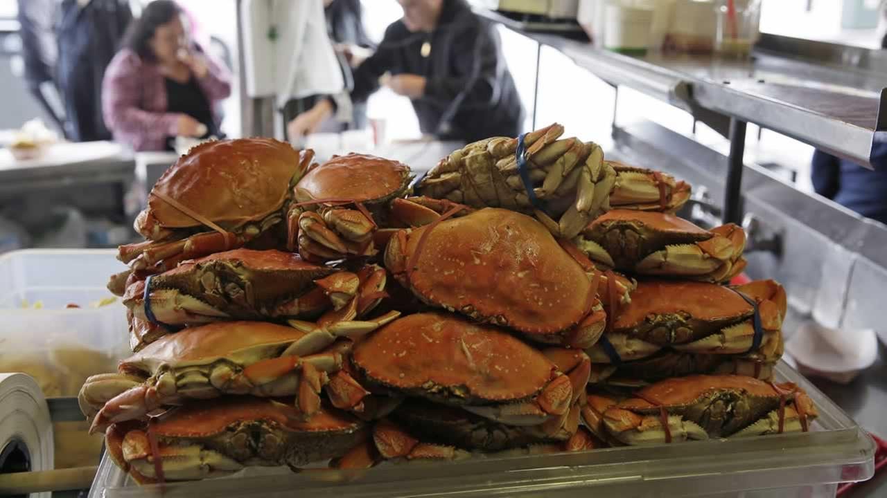 A stack of imported Dungeness crabs are shown for sale as people eat them in the background at Fishermans Wharf Tuesday, Dec. 22, 2015, in San Francisco.