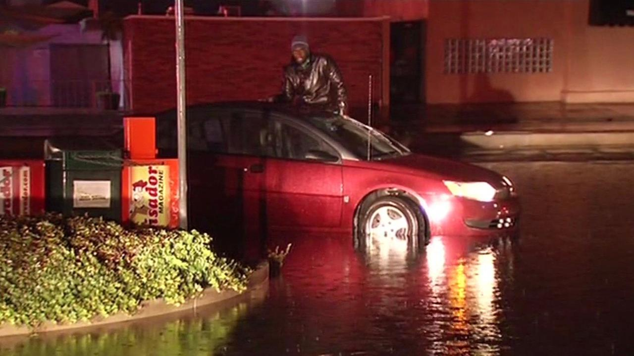 This photo shows a man stuck on a car on Bascom Avenue in San Jose, Calif. after his car stalled in the flood waters on Tuesday, January 6, 2016.KGO-TV