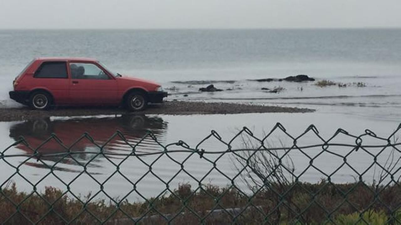 A red car was stuck on a flooded frontage road near the Bay Bridge Toll Plaza between San Francisco and Oakland, Calif. on Tuesday, January 5, 2016.