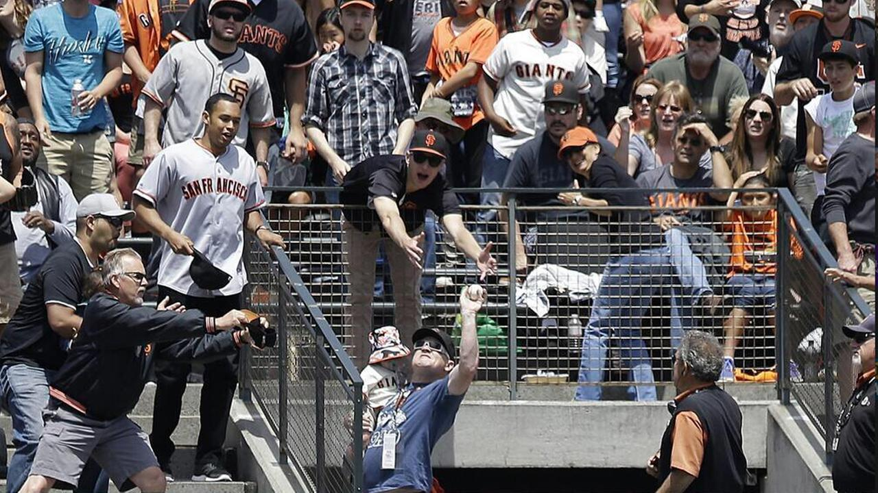 San Francisco Giants fan makes one-handed catch while holding baby.