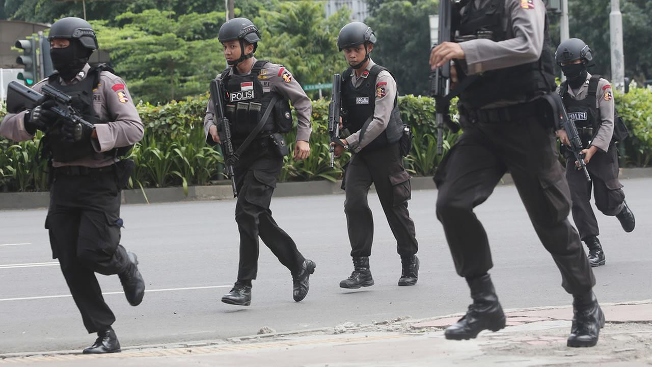 Police officers run with guns in Jakarta, Indonesia