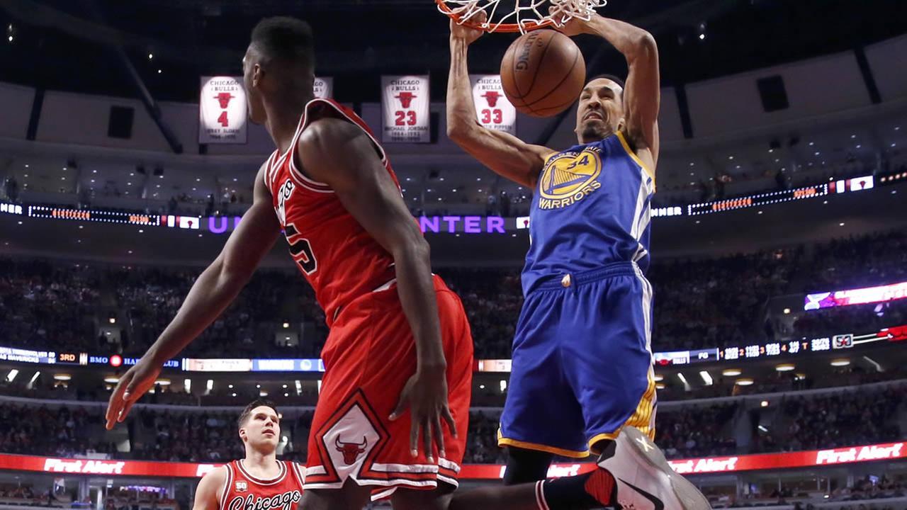 Golden State Warriors guard Shaun Livingston dunks over Chicago Bulls forward Bobby Portis during an NBA basketball game on Wednesday, Jan. 20, 2016, in Chicago.