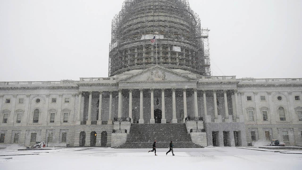 Two runners jog as the snow falls on Capitol Hill, Friday, Jan. 22, 2016, in Washington. (AP Photo/Alex Brandon)