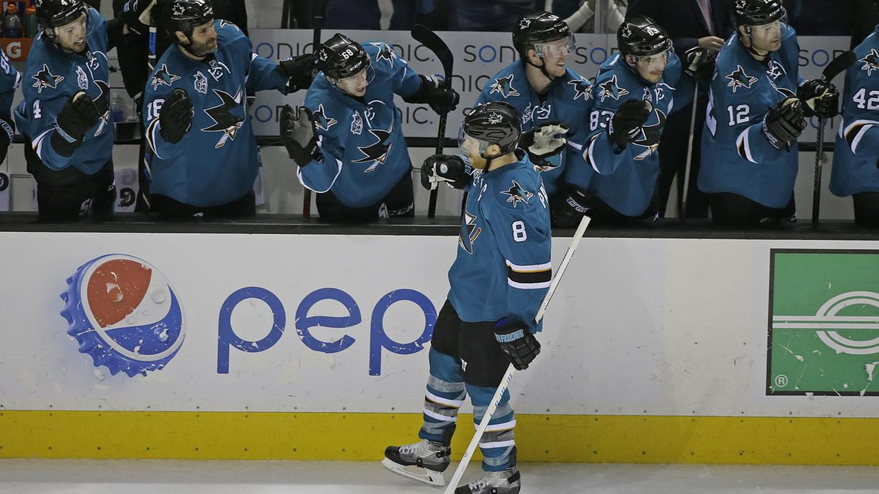 San Jose Sharks center Joe Pavelski (8) is greeted by his teammates after scoring a goal against the Minnesota Wild in their NHL hockey game Saturday, Jan. 23, 2015.