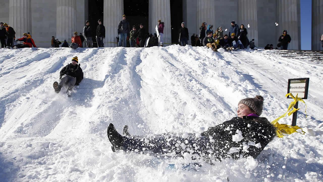 A woman bounces at the bottom as she sleds down the snow-covered steps of the Lincoln Memorial, Sunday, Jan. 24, 2016 in Washington. (AP Photo/Alex Brandon)