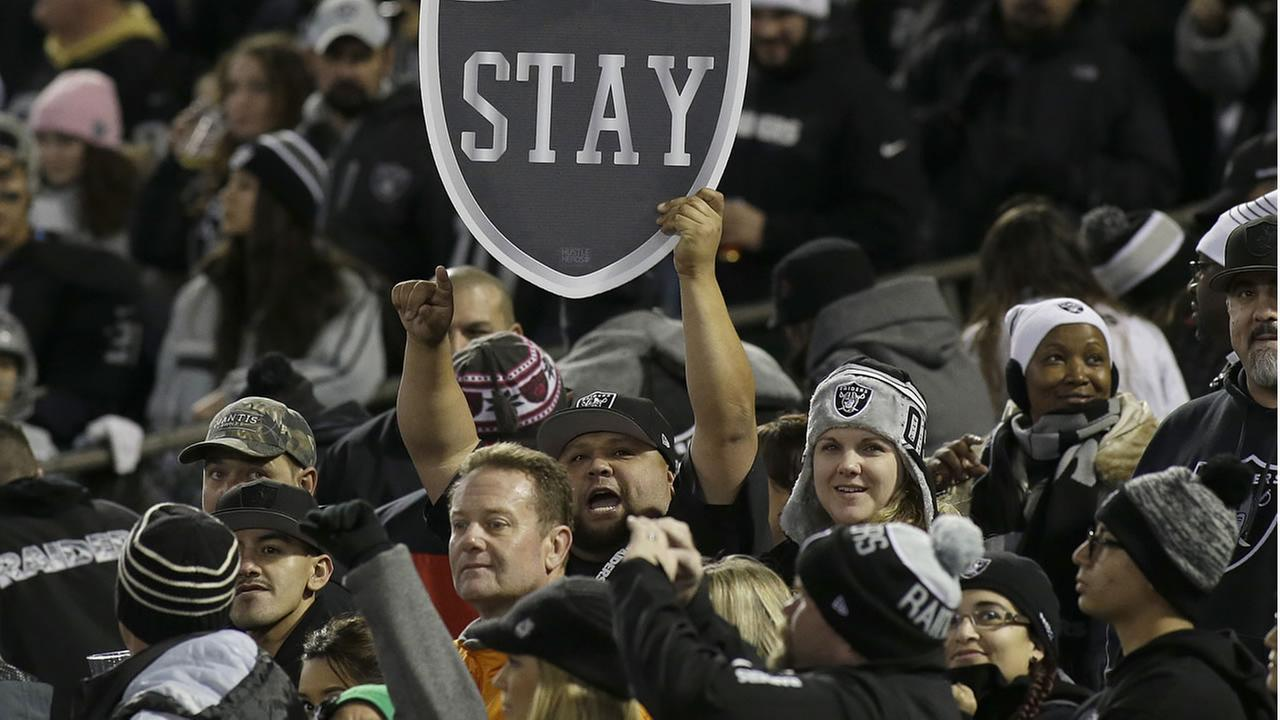 Fans hold up a sign for the Raiders to stay in Oakland before an NFL football game between the Raiders and the Chargers in Oakland, Calif., Thursday, Dec. 24, 2015. (AP Photo)