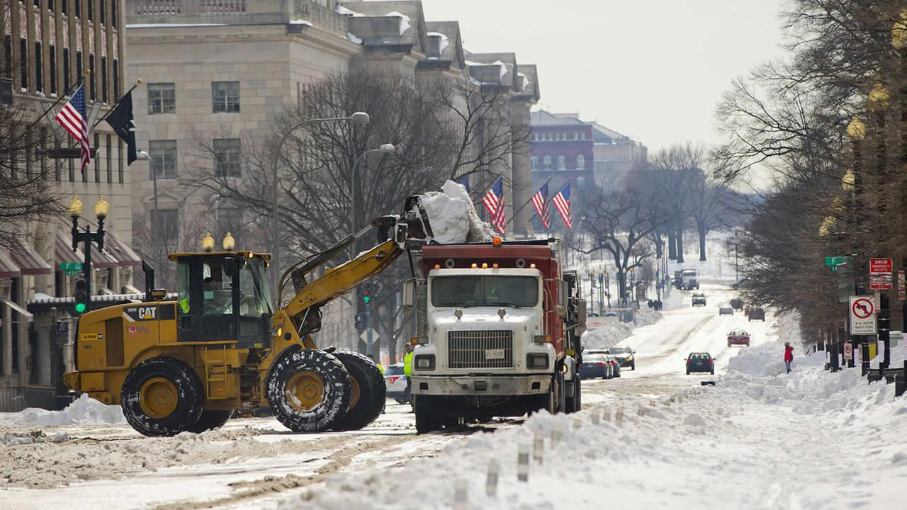 Heavy equipment is sued to fill a dump truck with snow as the clearing begins on 15th Street near the White House in Washington, Monday, Jan. 25, 2016.