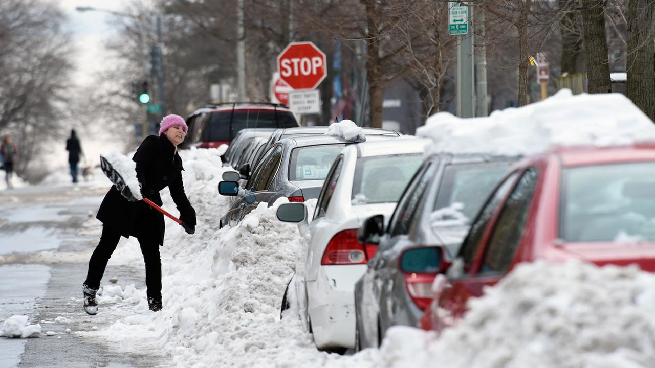 Grace McGuire of Washington shovels out her car in Washington, Tuesday, Jan. 26, 2016.