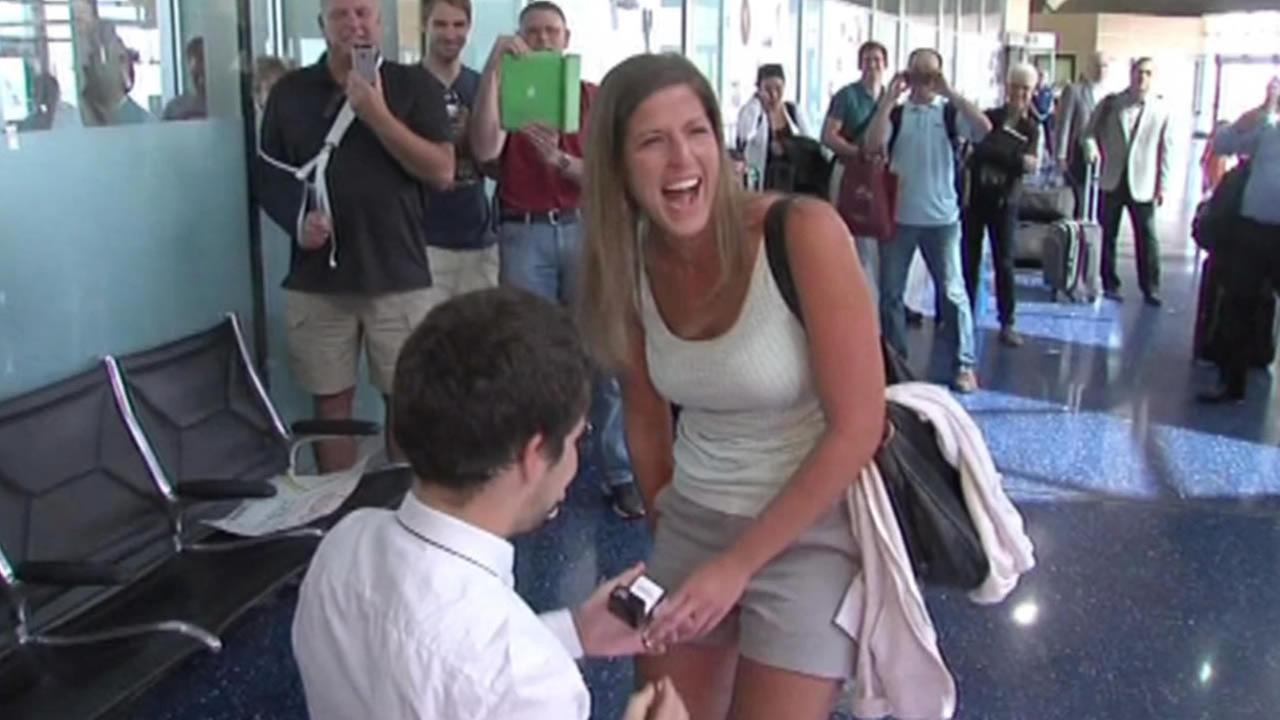 Man proposes to girlfriend at airport.