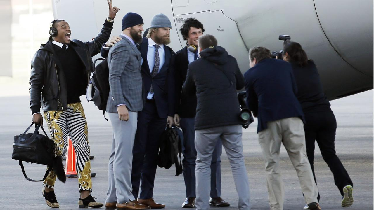 Carolina Panthers Cam Newton jumps into a picture being taken after getting off the plane at the Mineta San Jose International Airport on Sunday, Jan. 31, 2016, in San Jose, Calif.