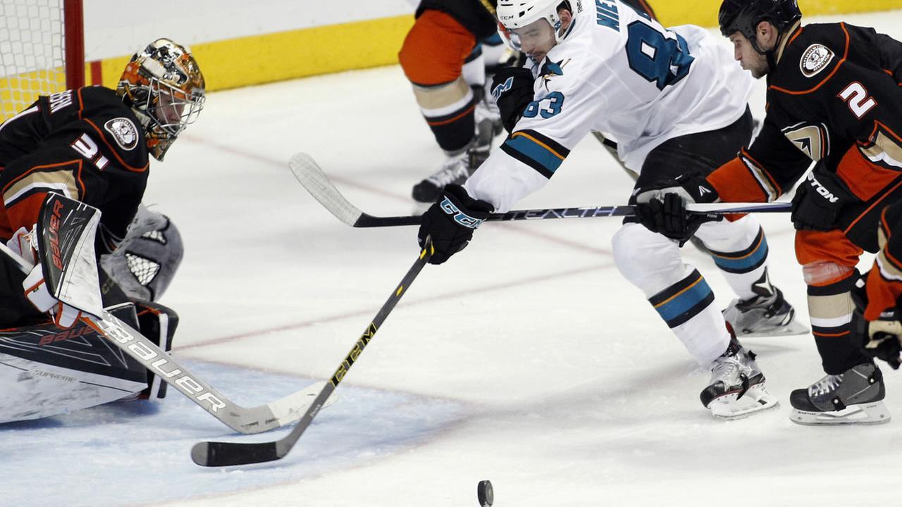 Anaheim Ducks goalie Frederik Andersen, left, of Denmark, knocks the puck away from San Jose Sharks left wing Matt Nieto (83), during an NHL  hockey game Tuesday, Feb. 2, 2016.