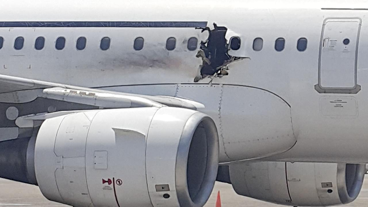 In this Tuesday, Feb. 2, 2016 photo, a hole is photographed in a plane operated by Daallo Airlines as it sits on the runway of the airport in Mogadishu, Somalia.