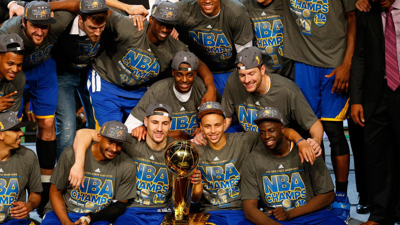 The Golden State Warriors celebrate with the Larry OBrien Trophy after Game 6 of basketballs NBA Finals in Cleveland, Wednesday, June 17, 2015.