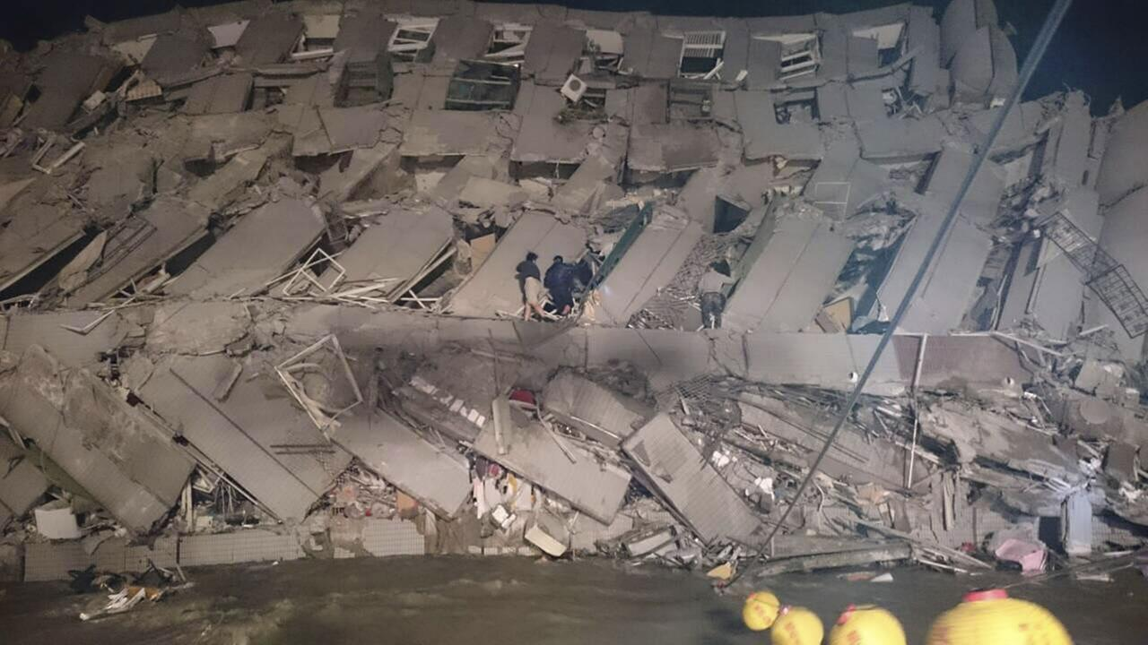Rescuers are seen entering an office building that collapsed on its side from an early morning earthquake in Tainan, southern Taiwan, Saturday, Feb. 6, 2016.