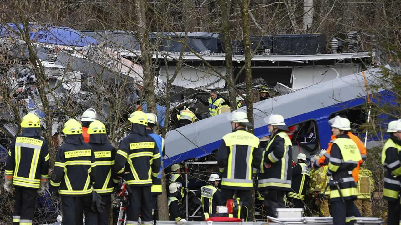 Rescue personnel stand in front of two trains that collided head-on near Bad Aibling, southern Germany, Tuesday, Feb. 9, 2016.