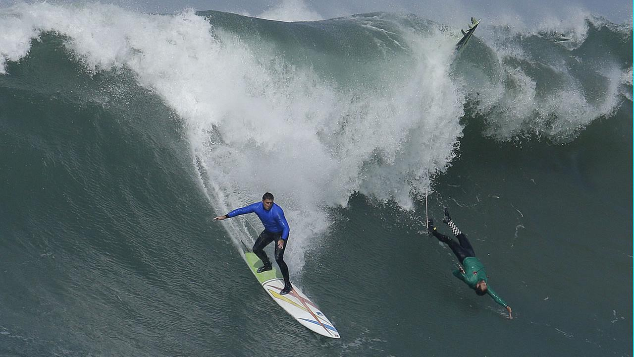 Ben Wilkinson, left, surfs beside Greg Long who wipes out on a giant wave during the third heat of the Mavericks surfing contest Friday, Feb. 12, in Half Moon Bay, Calif.AP Photo/Ben Margot