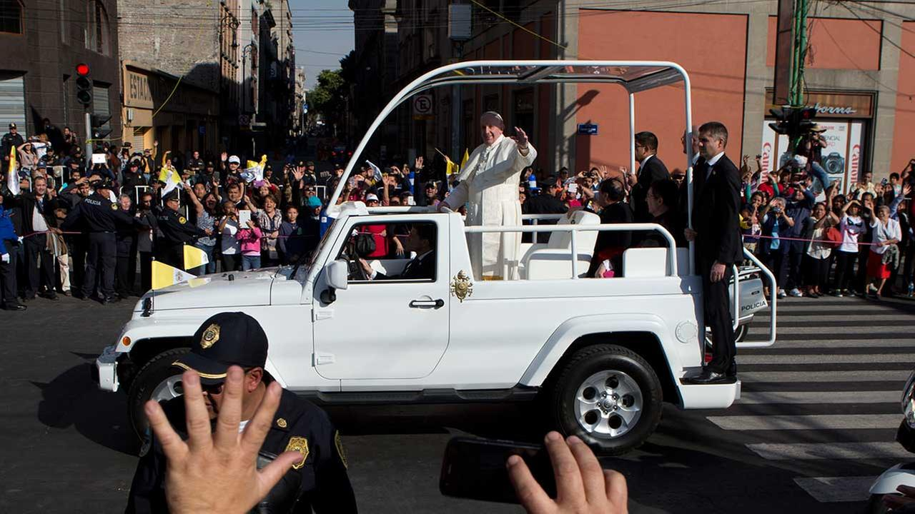 Pope Francis waves to people lining his route to the Basilica of the Virgin of Guadalupe in Mexico City, Saturday, Feb. 13, 2016.