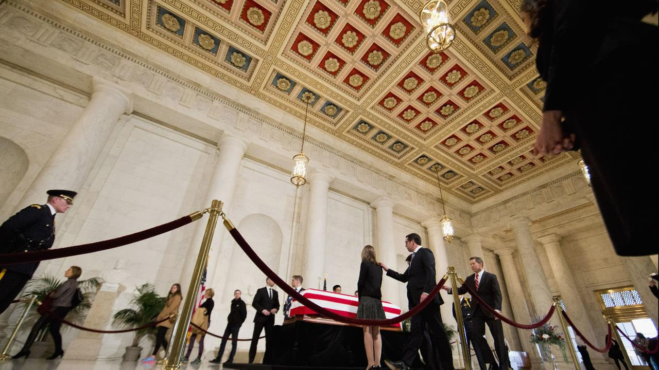 Members of the public walk through the Great Hall of the Supreme Court in Washington, Friday, Feb. 19, 2016, where late Supreme Court Justice Antonin Scalia lies in repose.