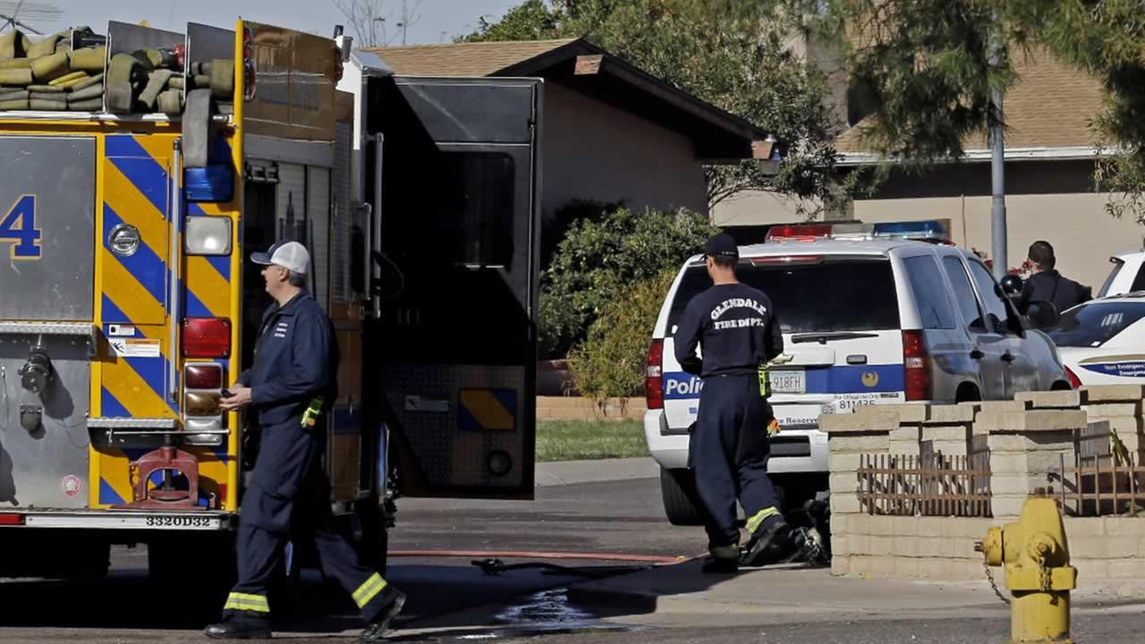 Police and fire officials walk near the scene of a fatal house fire and shooting Tuesday, Feb. 23, 2016, in Phoenix.