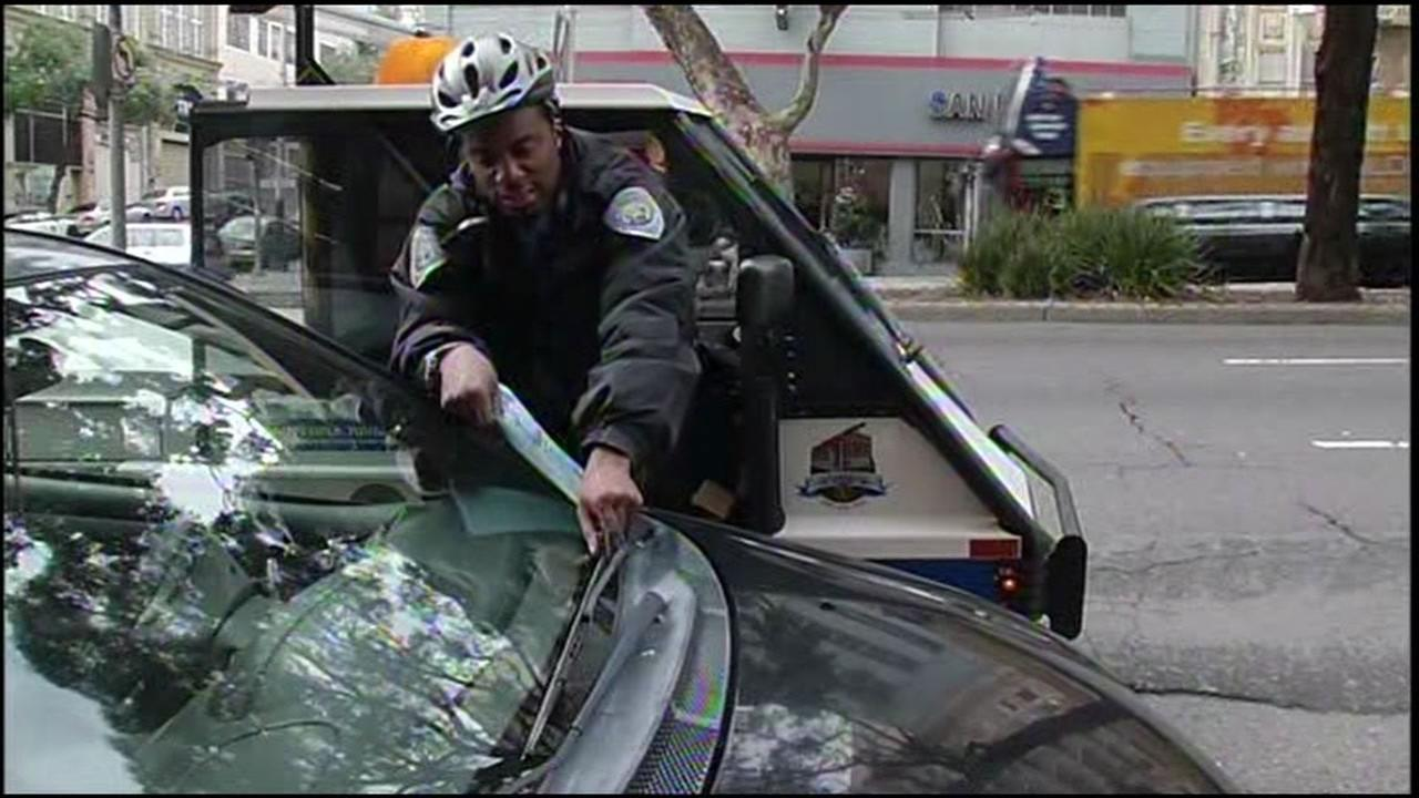 An undated image shows a San Francisco traffic enforcement officer giving a parking ticket.