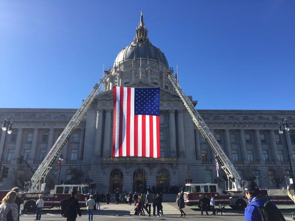 <div class='meta'><div class='origin-logo' data-origin='none'></div><span class='caption-text' data-credit='Elissa Harrington/KGO-TV'>An American flag hanging from the ladders of fire trucks is seen ahead of San Francisco Mayor Ed Lee's memorial service on Sunday, Dec. 17, 2017.</span></div>