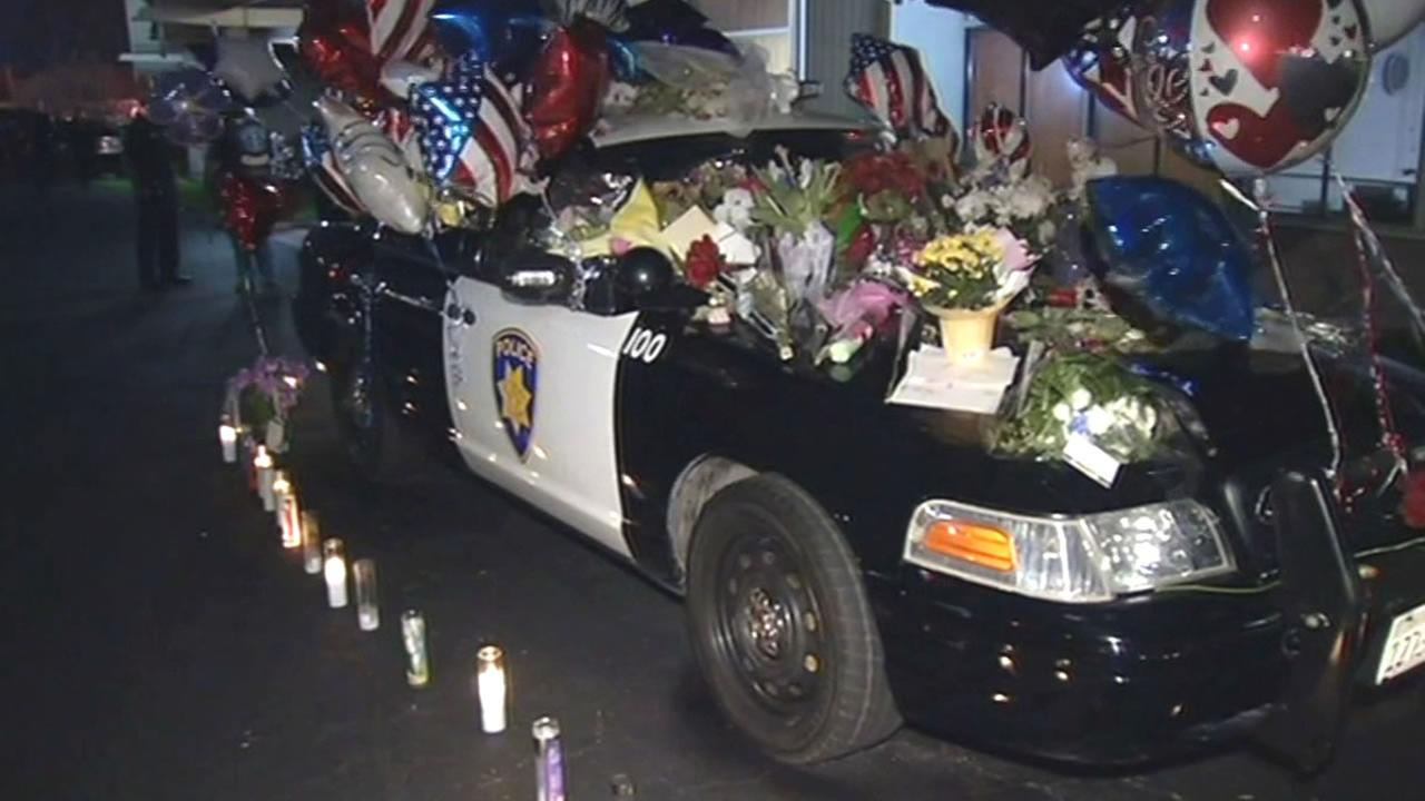 Officer Donnie Pearmans patrol car with flowers, balloons and candles