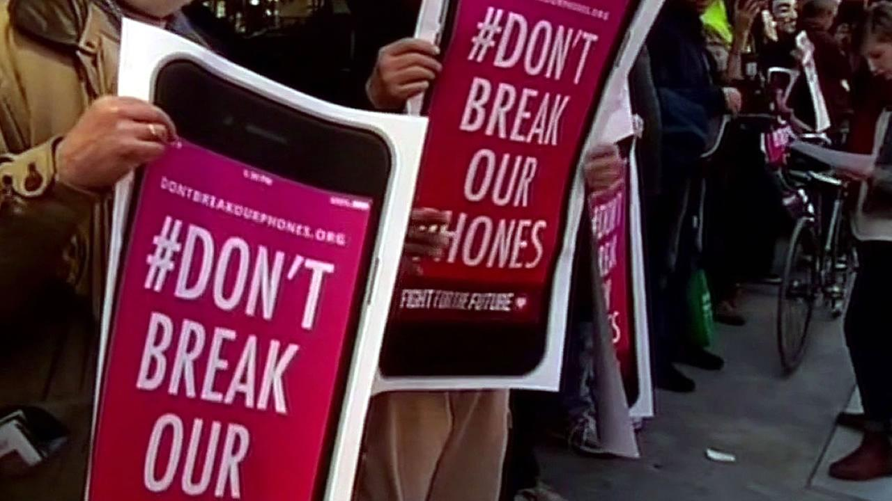 people hold signs that reads #Dont break our phones