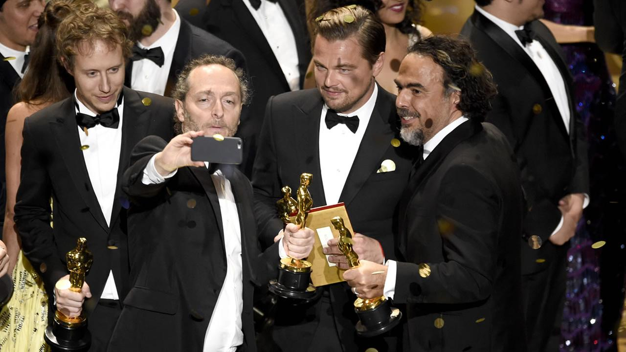 Emmanuel Lubezki, Leonardo DiCaprio, and Alejandro G. Inarritu take a selfie on stage after the Oscars on Sunday, Feb. 28, 2016 in Los Angeles. (Photo by Chris Pizzello/Invision/AP)