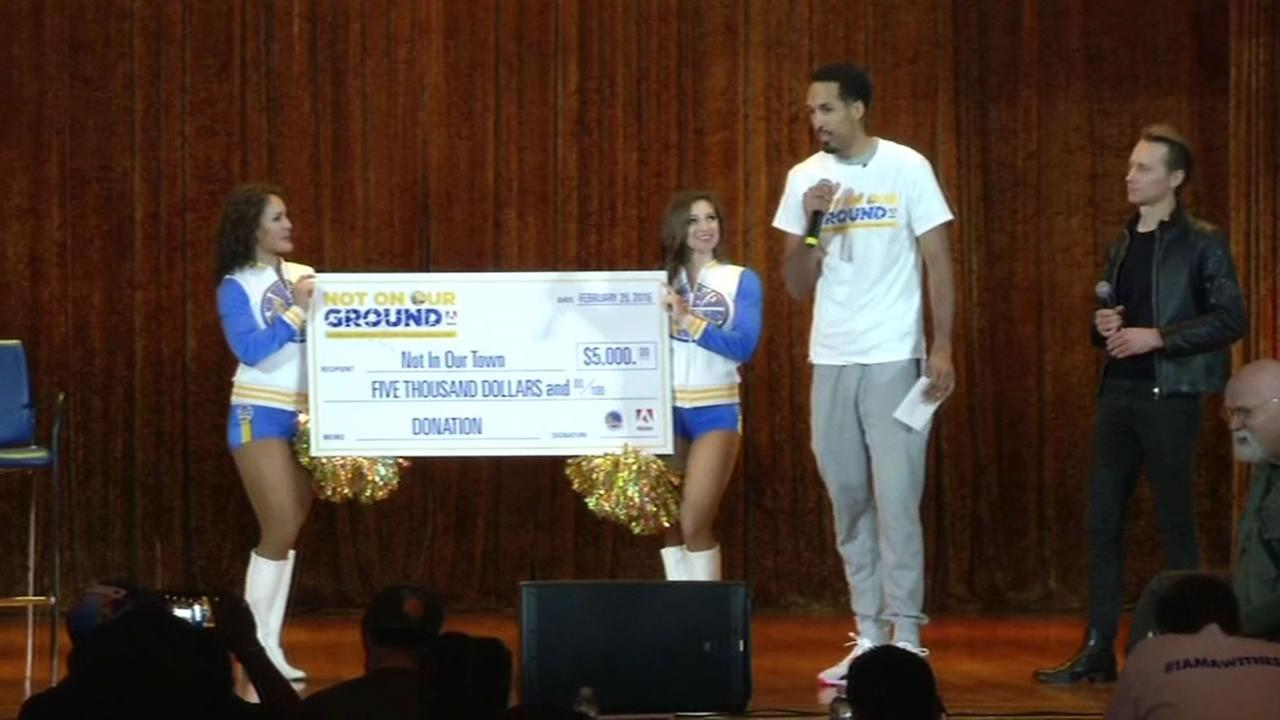 Warriors guard Shaun Livingston stands in front of a check donated by the team to help McClymonds High School in Oakland, Calif. stand up against bullying on February 29, 2016.